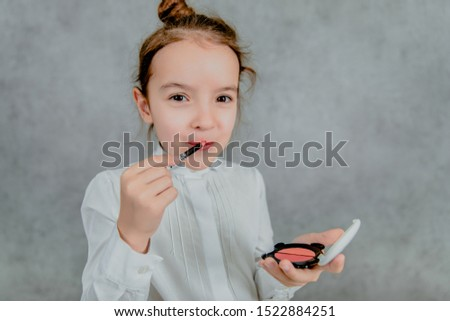 Little business lady Business lady on a gray background. The business lady is seriously and surely paints her lips. Formal fashion for a small business lady #1522884251