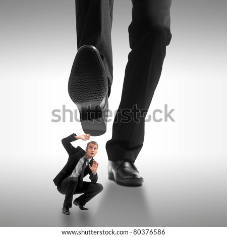 Little business man being crushed by the feet of a giant business man