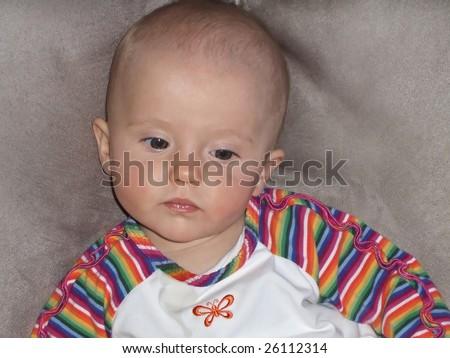 Little caucasian baby girl sitting on a sofa.