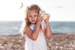Little caucasian blond girl holding seashell and listening to the sea