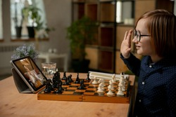 Little Caucasian boy chess player playing chess online using laptop.