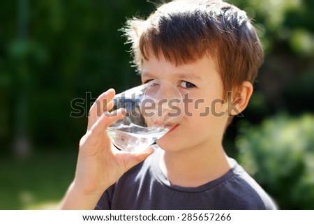 Little caucasian boy drink water in nature
