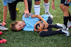 little caucasian boy fell to his knee, ache in joints during football game outdoors, injury during sport competition