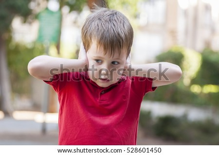 Little Caucasian boy in red polo shirt closing ears with his hands. Child does not want to hear. Protective pose, protectiveness, childhood traumatic experience.
