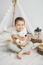 Little caucasian boy smiles and hugs a teddy bear in a light scandinavian christmas interior.