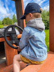 little caucasian boy wearing a baseball cap and hoody denim jacket sitting in wooden car pretend driving. Playground in countryside