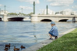 little caucasian boy wearinh checkered shirt, cap and denim shorts sitting on bank of Neva River, Saint petersbourg Russia, watching ducks. Image with selective focus