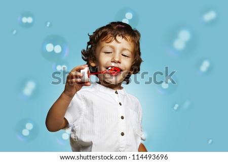little caucasian boy with soap bubbles on blue background