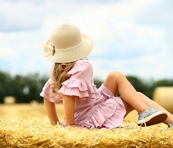 Little caucasian cute girl smiles in a wicker hat and a pink blue dress on a huge haystack on a mown wheat field. Agriculture. Rest in the village. Organic food and healthy lifestyle concept