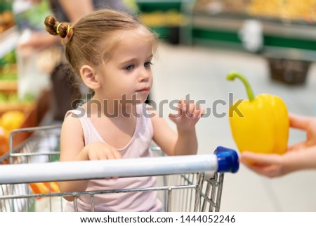 Little Caucasian girl chooses fresh vegetables in the supermarket. A child buys sweet pepper healthy food for the whole family.