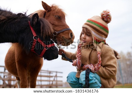 Little Caucasian girl getting animal-assisted therapy with tiny ponies on horse farm Stok fotoğraf ©