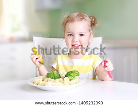 Little caucasian girl smiling face sitting at table eating vegetables,healthy lifestyle kid's nutrition concept.