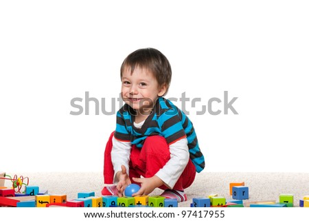 Little cheerful boy is playing with blocks on the carpet