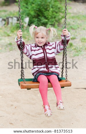 little cheerful girl in red and pink clothes playing on swing