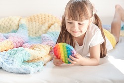 little cheerful girl plays in a multi-colored plastic toy pop it while lying on the bed. playing at home during summer holidays