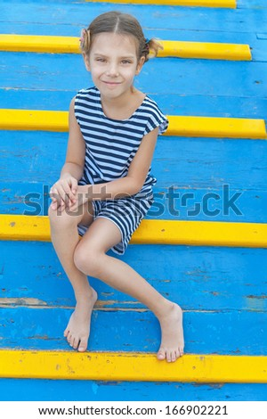 Little cheerful girl sitting on wooden bridge blue with yellow steps.