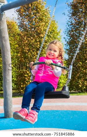 Stock Photo Little cheerful girl swinging on a swing. Sunny weekend. Baby happiness.