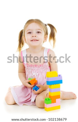 little cheerful girl with construction set over white background