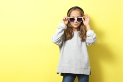 Little cheerful smiling girl in fashionable clothes on a colored background. Children's clothing, children's fashion