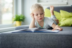Little, cheerful, three years old boy lying on his belly on the sofa, with open book in front of him.
