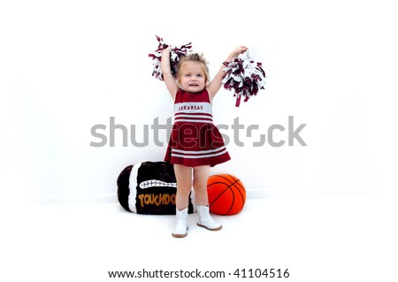 Little cheerleader dressed in burgundy and grey holds pom poms high in the air.  She is wearing white gogo boots and standing in front of a stuffed football and basketball.