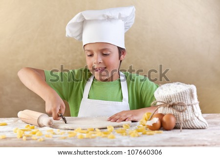 Little chef cutting the dough making pasta the traditional way