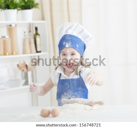 Little chef enjoying  in the kitchen making big mess