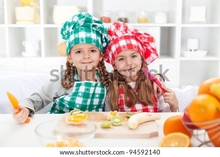 Little chef girls slicing fruits in the kitchen - healthy eating