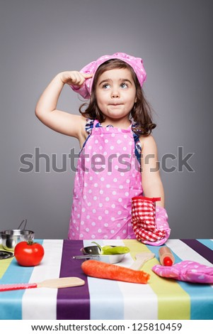 little chef in pink uniform thinking what to cook - stock photo