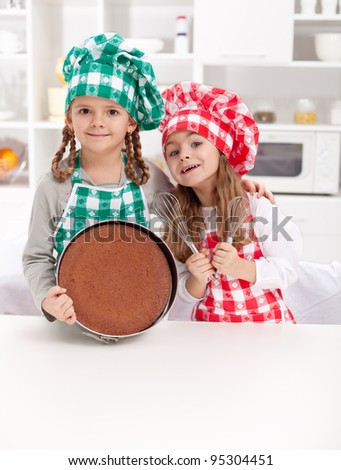 Little chefs baking a cake - smiling with cooking utensils in the kitchen