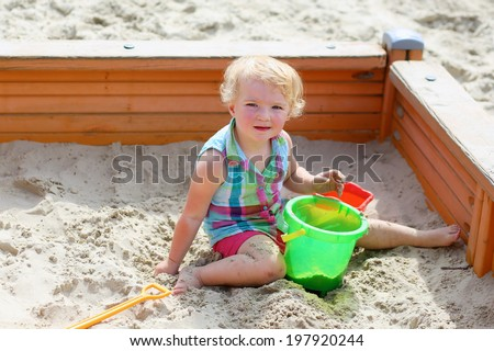 Little child, adorable blonde toddler girl, enjoying hot sunny summer day at the playground sitting inside big sandbox building castles and playing with sand, shovel and toy bucket  - stock photo