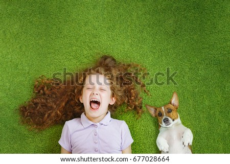 Stock Photo Little child and cute dog resting on green carpet.
