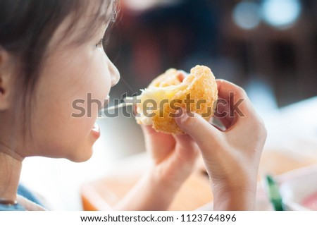 Little child asian girl eating sticky stretch fried cheese ball.Her feeling enjoyment.