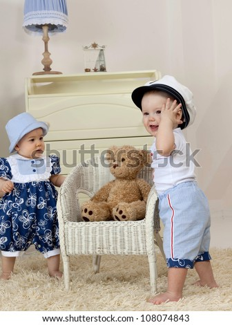 little child baby boy and girl standing near the chair  indoors in baby room playing