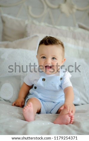little child baby boy.Cute boy sitting on the white blanket at the bed.Little baby boy
