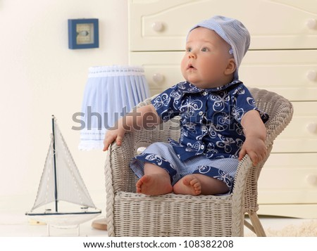 little child baby boy sitting on the chair indoors in baby room fashion clothing