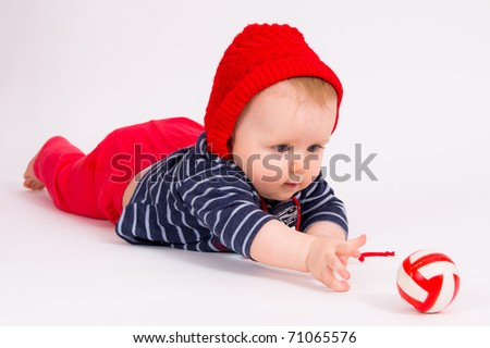 Little child baby crawling for the red ball