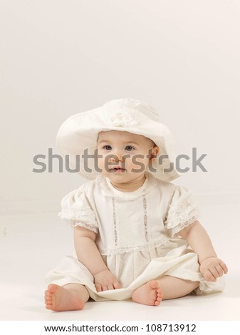 little child baby girl sitting on the floor indoors studio shot dress fashion