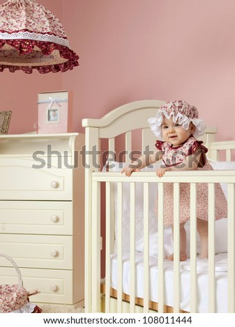 little child baby girl standing in bed indoors in baby room hat dress fashion