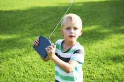 Little child blond boy playing with toy radiocontrolled airplane against green grass lawn background. Holds and operates radio controls