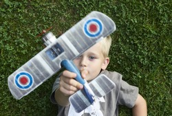 Little child blond boy playing with toy radiocontrolled airplane against green grass lawn background. Holds and operates radio controls - transmitter receiver. Dreaming about traveling and discovering