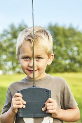 Little child blond boy playing with toy radiocontrolled airplane against green grass lawn background. Holds and operates radio controls - transmitter receiver