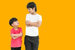 Little child boy and tall child boy standing arms crossed and looking face isolated on yellow background. Big and small kid concept at be friends. Back to school for concept.