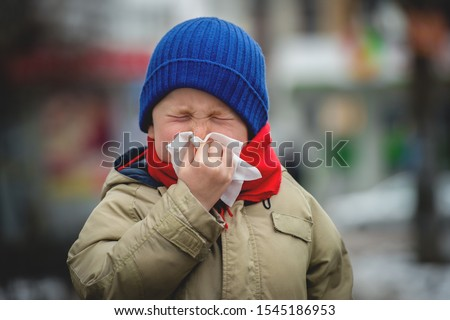 Little child boy in scarf and hat blow his nose. Sick child with napkin in autumn park. Allergic kid, flu season. Kid with cold rhinitis, get cold. Back to school Stock photo ©
