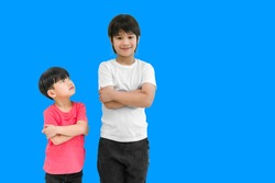 Little child boy in wear red t shirt standing and arms crossed looking for face of tall child at standing arms crossed and smile isolated on blue background. Big and small boy concept with be friends.