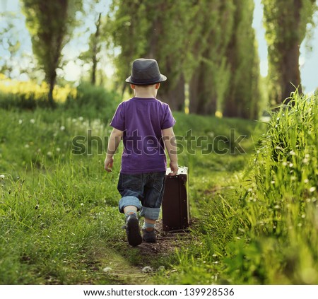 Little child carrying a suitcase