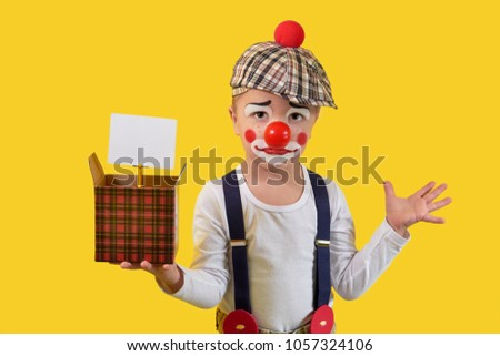 Little child clown in suit,make-up,red nose shows funny emotion face,surprise,sadness,uncertainty.Portrait kid boy joker,humorist,yellow background studio.In hand holds cardboard box,blank for text. #1057324106