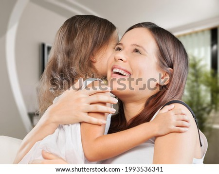 Little child congratulating mom with Mother's day at home and hugging.