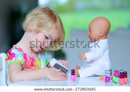 Little child, cute toddler girl having fun playing at home with colorful nail polish doing manicure and painting nails to her doll