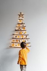 Little child decorating handmade craft Christmas tree made from sticks and natural materials hanging on wall. Sustainable Christmas, zero waste, plastic free, eco friendly.